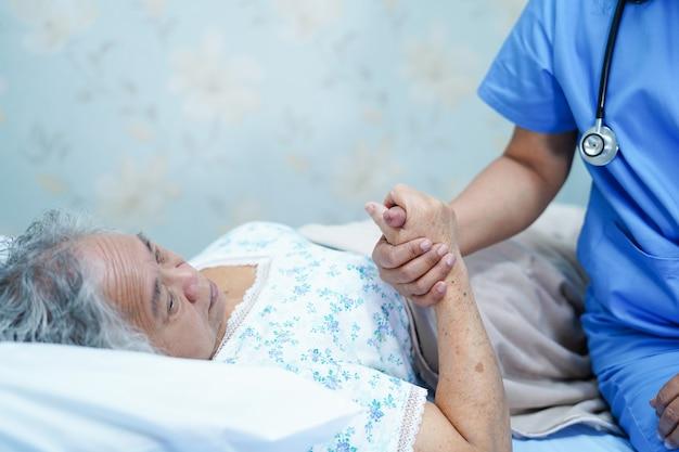 O cuidado asiático do doutor do fisioterapeuta da enfermeira, ajuda e apoia o paciente idoso da mulher da senhora idosa.