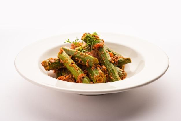 O curry de coxinha é um molho de vegetais saboroso e picante ou receita seca que é preparado com palitos de moringa e especiarias