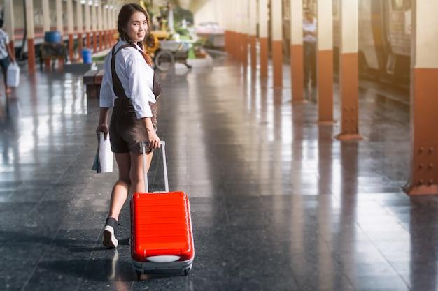 O curso grávido da mulher asiática que leva seu saco e mapa vermelhos do trole na estação de trem viaja.