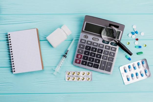 O custo do conceito de saúde consiste em várias pílulas e calculadora do estetoscópio. fundo de madeira azul.