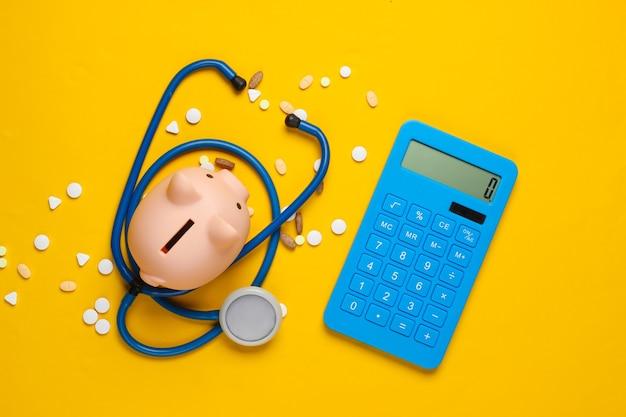 O custo do medicamento. cofrinho com estetoscópio, comprimidos e calculadora em amarelo