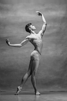O dançarino de balé masculino posando sobre cinza