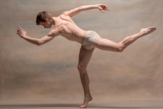 O dançarino de balé masculino posando sobre espaço cinza