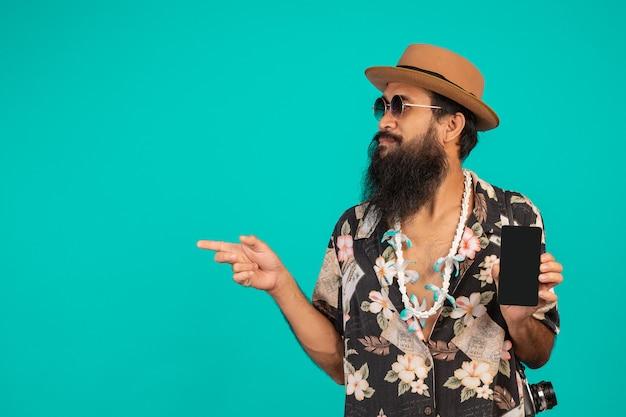 O de um homem de barba longa feliz usando um chapéu, vestindo uma camisa listrada, segurando um telefone em um azul.