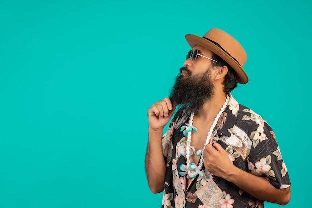 O de um homem feliz, com uma barba longa, usando um chapéu, vestindo uma camisa listrada, mostrando um gesto em um azul.