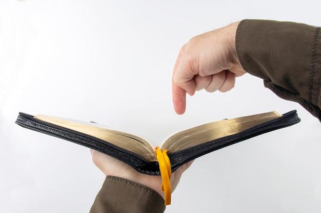 O dedo indicador aponta para o texto na bíblia aberta