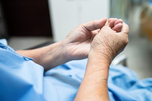 O dedo paciente asiático do gatilho da dor da mulher sênior trava sua mão ao sentar-se no hospital.