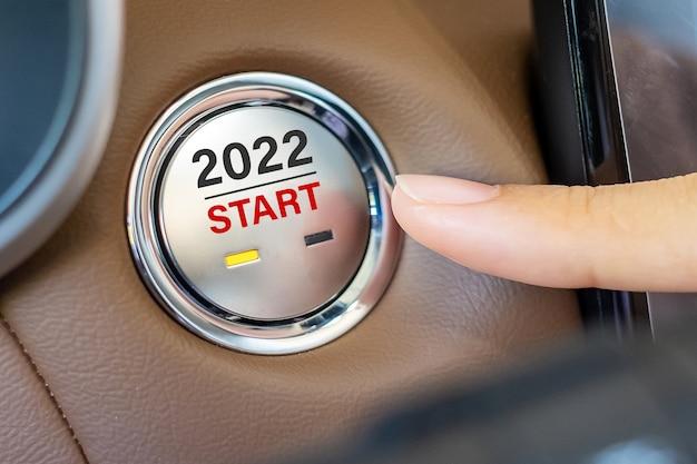 O dedo pressiona o botão de ignição de um carro com o texto 2022 iniciar