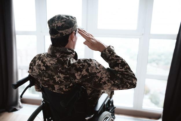 O deficiente em uniforme militar senta em uma cadeira de rodas