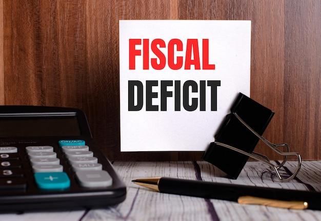 O deficit fiscal é escrito em um cartão branco sobre um fundo de madeira, ao lado de uma calculadora e uma caneta.
