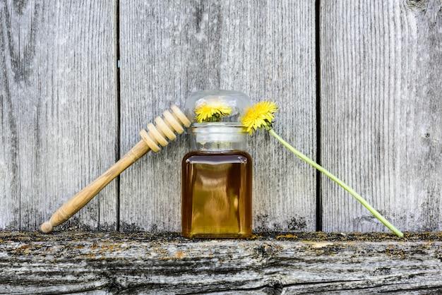 O dente-de-leão floresce o mel no fundo de madeira velho, vintage.