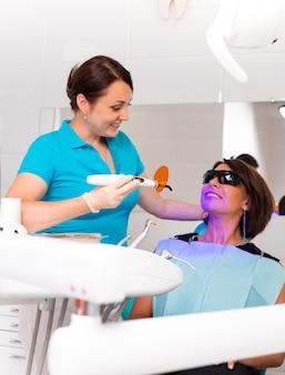 O dentista brilha nos dentes do paciente com uma lâmpada ultravioleta para fixar o selo dentário.