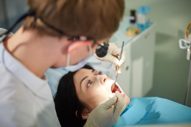 O dentista começa a examinar a cavidade oral de uma menina bonita