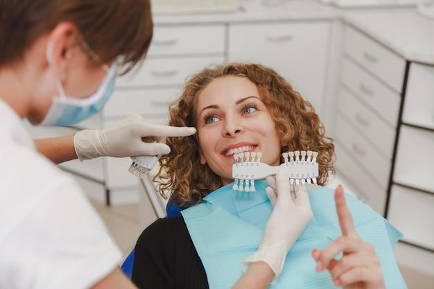 O dentista comparando a cor dos dentes do paciente com amostras para tratamento de clareamento