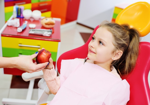 O dentista dá a menina vermelha madura de apple na cadeira dental. dentista pediátrico