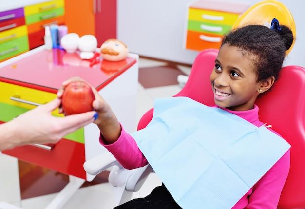 O dentista dá uma maçã vermelha madura a uma menina americana africana preta pequena em uma cadeira dental.