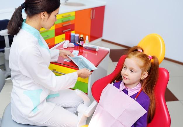 O dentista das crianças examina os dentes e a boca da criança - uma menina ruivo bonito que senta-se em uma cadeira dental