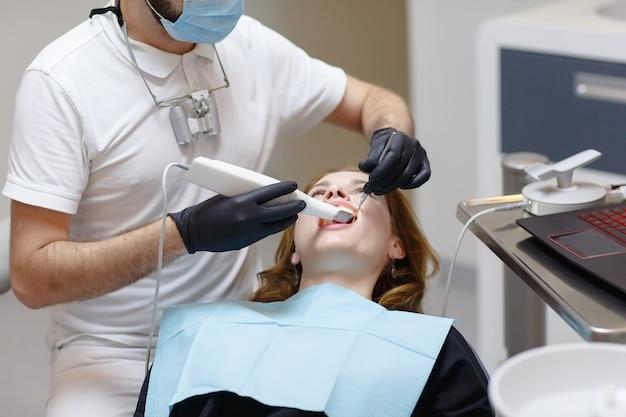 O dentista escaneia os dentes do paciente com um scanner 3d.