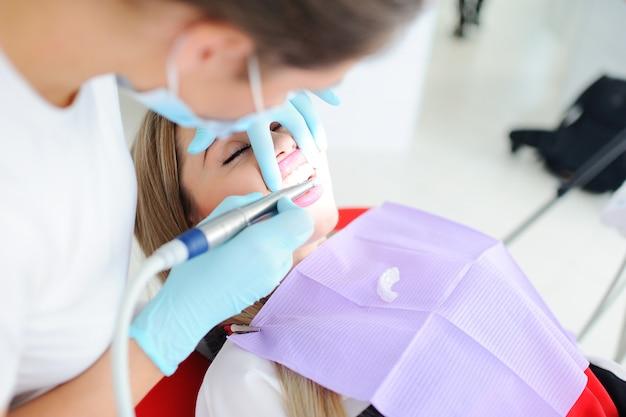 O dentista está tratando os dentes com o paciente