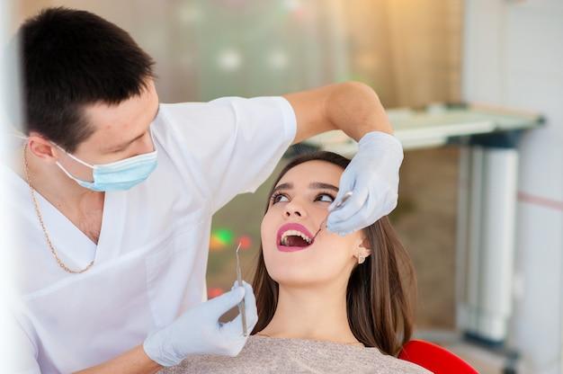 O dentista está tratando os dentes com uma menina bonita.