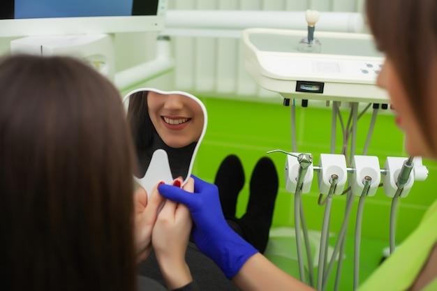 O dentista está tratando os dentes para o cliente no consultório odontológico