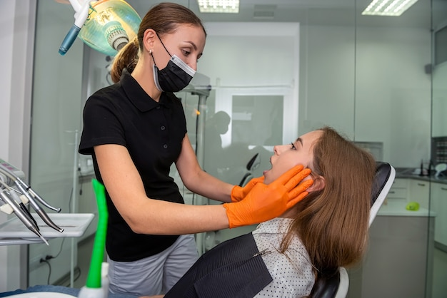 O dentista examina o paciente com aparelho ortodôntico. assistência médica