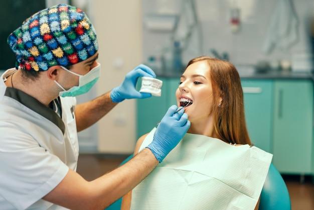 O dentista examina o paciente fêmea com as cintas no escritório do denal.