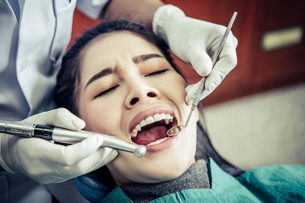 O dentista examina os dentes do paciente.