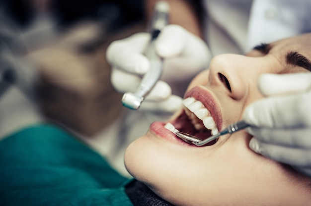 O dentista examina os dentes do paciente.