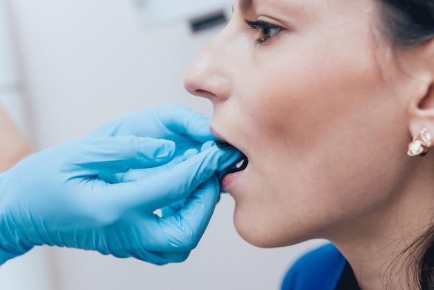 O dentista faz a imagem do raio x para a jovem mulher na clínica dental. visando radiografia dentária.