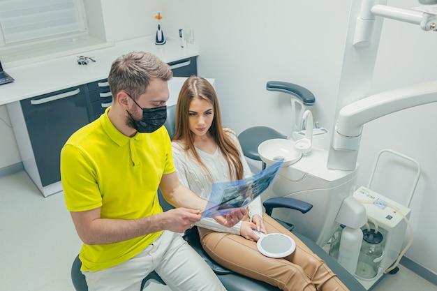 O dentista mostra a foto de um raio-x dos dentes do paciente em uma clínica odontológica moderna