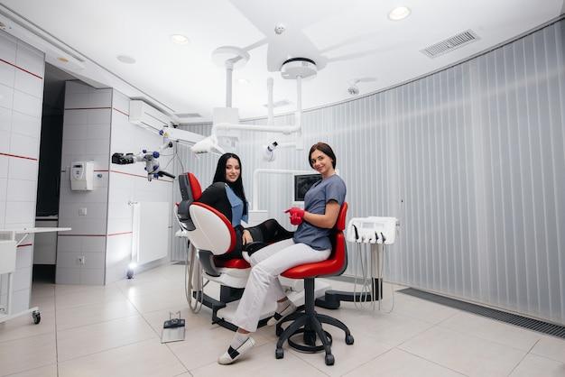 O dentista mostra uma imagem dos dentes do paciente e informa o tratamento necessário. odontologia, saúde.