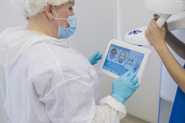 O dentista na clínica faz um raio-x do paciente