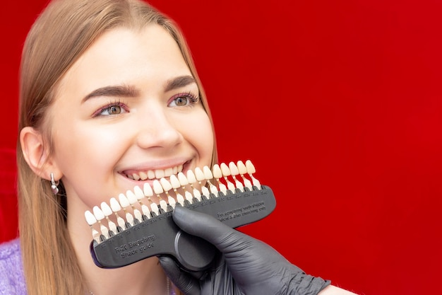 O dentista para procedimento de clareamento dos dentes seleciona a cor inicial do guia de cores para clareamento dos dentes da menina