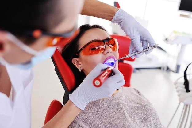 O dentista sela o dente para o paciente - uma menina muito jovem