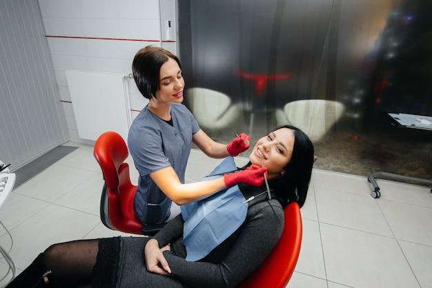 O dentista trata os dentes da garota no paciente. odontologia.