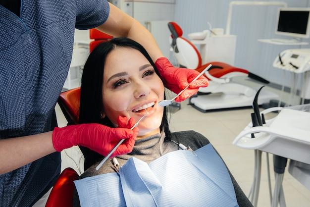 O dentista trata os dentes da garota no paciente. odontologia