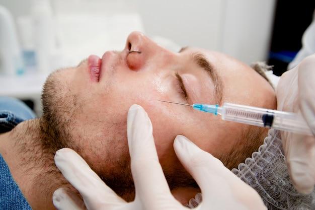 O dermatologista está aplicando injeções no rosto do homem para remover cicatrizes e rugas e torná-lo liso e jovem.