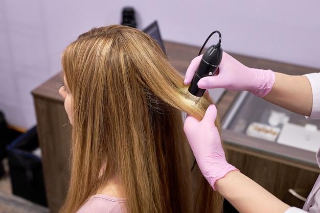 O dermatologista médico cortada diagnostica a estrutura do cabelo de uma jovem usando o tricoscópio de ferramenta.