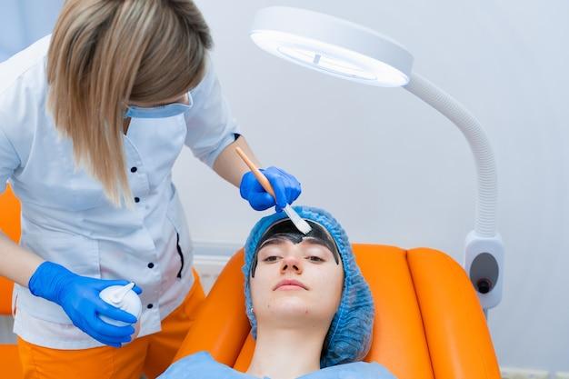O dermatologista passa máscara preta no rosto para fotorejuvenescimento a laser e peeling de carbono. dermatologia e cosmetologia. usando laser cirúrgico.