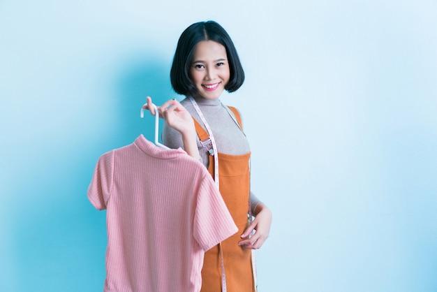 O desenhista asiático da menina está mostrando fora a camisa que está projetando.