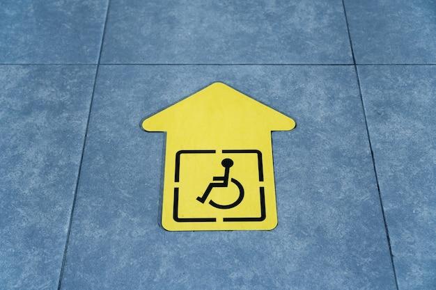 O desenho de uma cadeira de rodas em uma seta amarela colada ao ladrilho na sala de espera