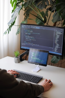 O desenvolvedor está codificando usando a tela e o tablet. freelancer está trabalhando em casa, no escritório doméstico, com a planta