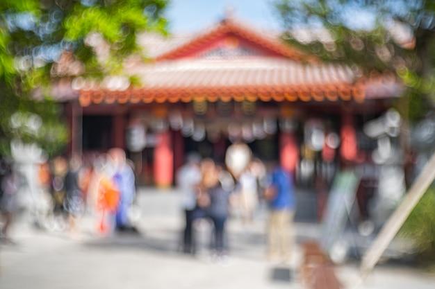 O desfocado do santuário japonês com pessoas em frente ao santuário