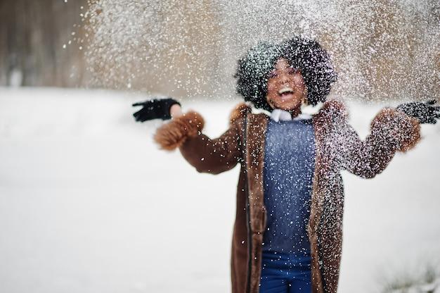 O desgaste de mulher afro-americano do cabelo encaracolado no casaco de pele de carneiro e as luvas colocadas no dia de inverno vomitam a neve.