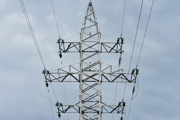 O design das linhas de força do poste de metal com fios contra o céu