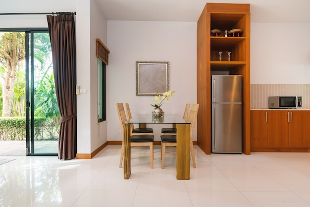 O design de interiores da casa, casa e villa inclui mesa para refeições, cadeira, geladeira, micro-ondas
