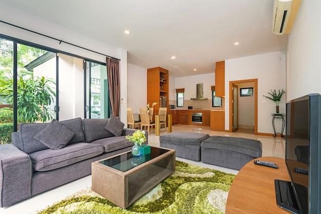 O design de interiores da casa, da casa e da villa inclui sofá, televisão na sala de estar e mesa de jantar