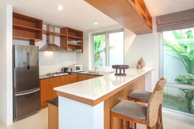 O design de interiores na área de cozinha que caracteriza balcão de ilha e embutiu mobília