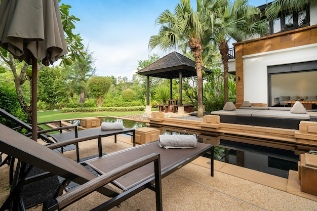 O design exterior da casa, casa e villa apresenta piscina, espreguiçadeira, guarda-sol e toalha no terraço da piscina
